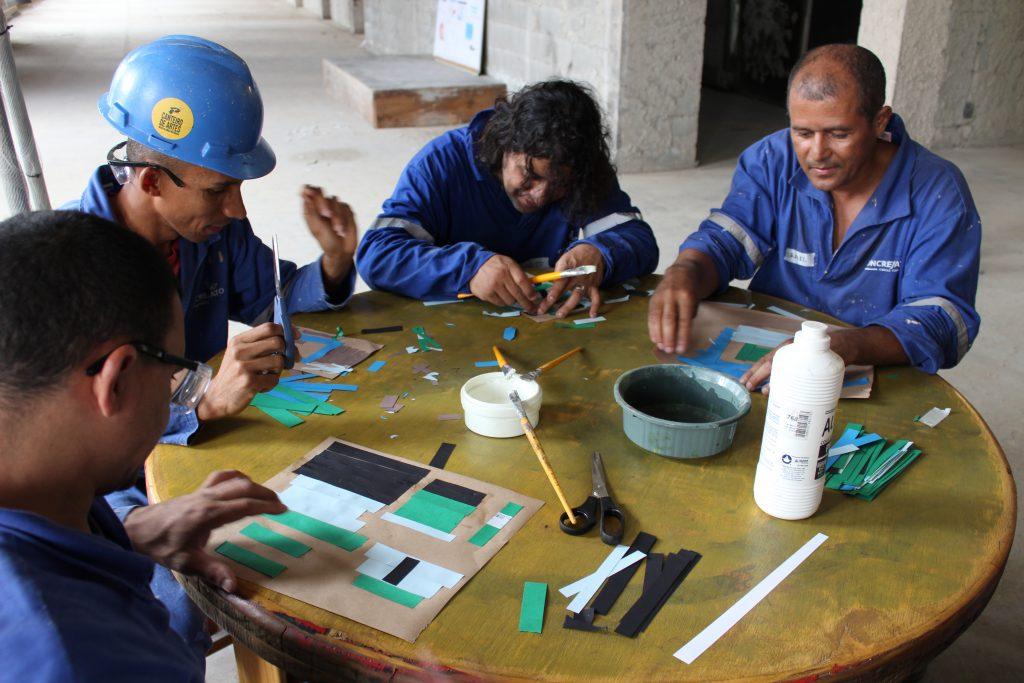 Foto de homens em volta de uma mesa redonda fazendo colagens com papeis coloridos.