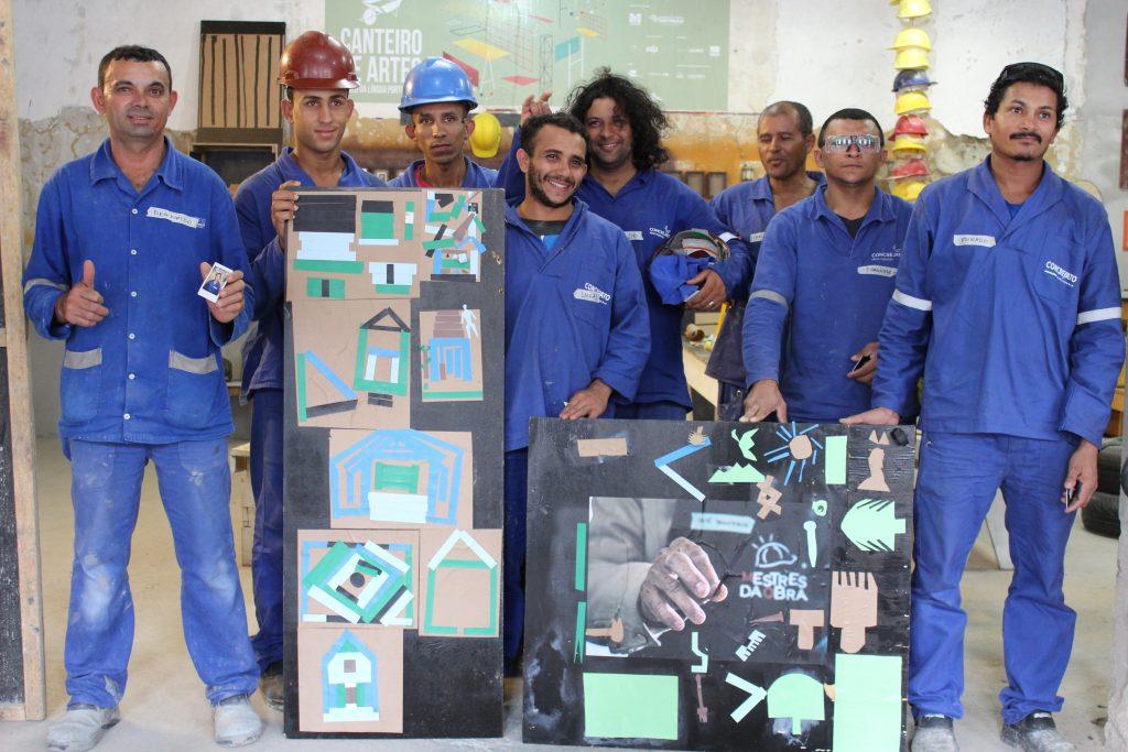 Foto de oito homens em pé durante a oficina Canteiro de Artes.